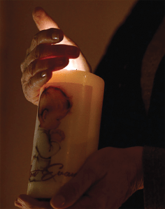 Courtesy Photo(s)  A woman holds a candle that displays a baby praying.