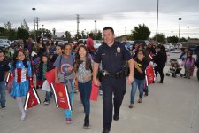 courtesy photo/rialto police dept. Cpl. Cameron Nelson of the Rialto Police Department walks with superhero students from Curtis Elementary May 22 during an anti-bullying campaign.