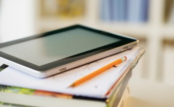 USA, New Jersey, Jersey City, Digital tablet on stack of books --- Image by © Tetra Images/Tetra Images/Corbis