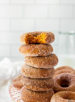 baked pumpkin donuts in a stack with top donut with a bite