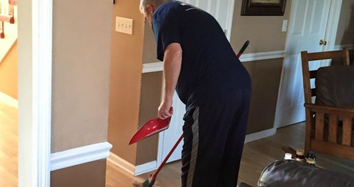 man sweeping house