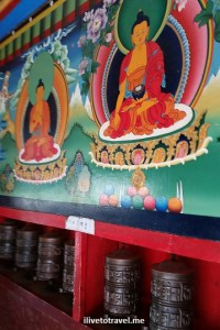 Wall painting and the ever-present prayer wheels at the kani gate