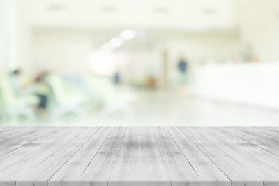 Empty white wood table top on blur hospital interior for background,space for montage products ...