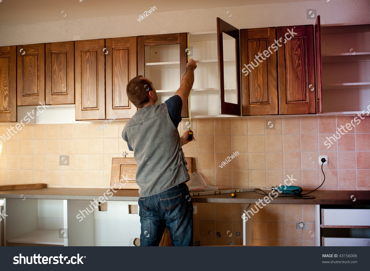 stock photo carpenter working on new kitchen cabinets new kitchen cabinets Carpenter working on new kitchen cabinets