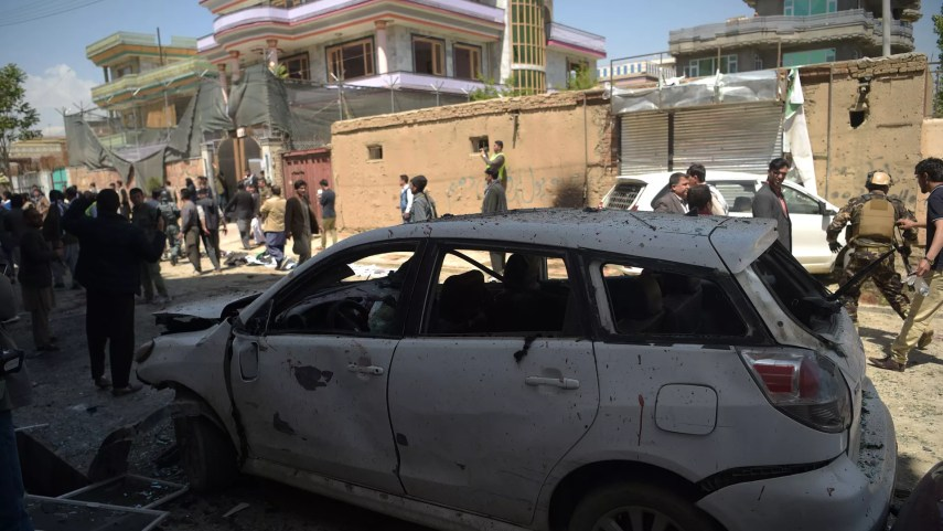 A burned-out car and crowds in the street where the bombing took place