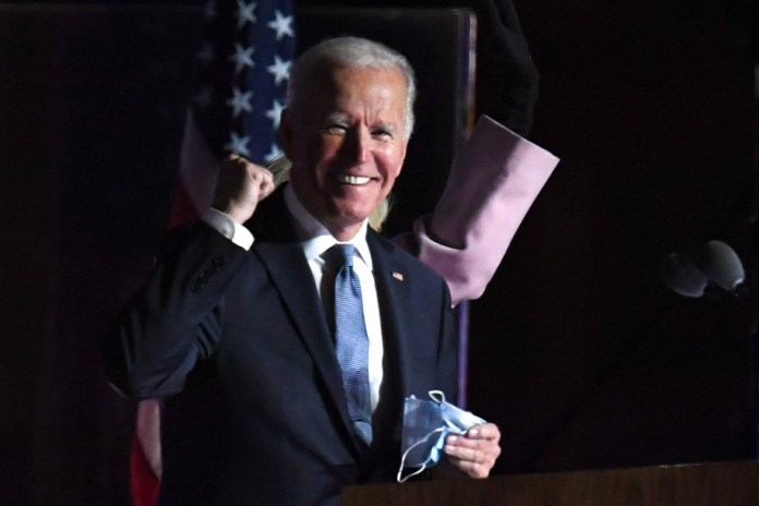 Democratic presidential nominee Joe Biden gestures as he arrives onstage to address supporters during election night at the Chase Center in Wilmington, Delaware, early on November 4, 2020. (Photo by Roberto SCHMIDT / AFP) (Photo by ROBERTO SCHMIDT/AFP via Getty Images)
