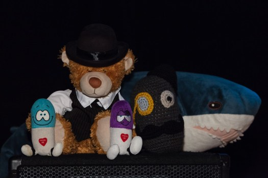 Roustabear gathered with the crew and a shark on top of a speaker