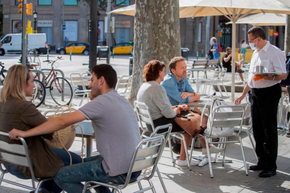 """Barcelona reabre los bares al aire libre, con """"trabajadores esenciales"""" en riesgo."""
