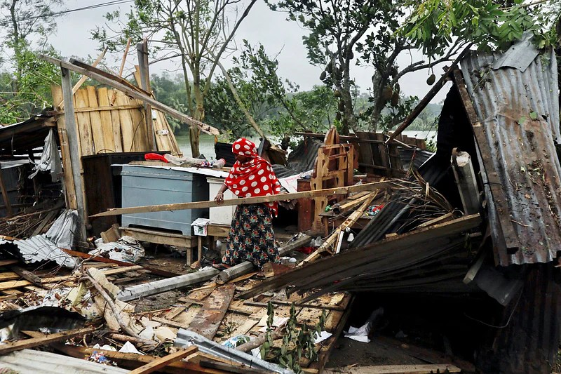 A woman clears her house that was demolished by the cyclone Amphan in Satkhira, Bangladesh 21 May, 2020.
