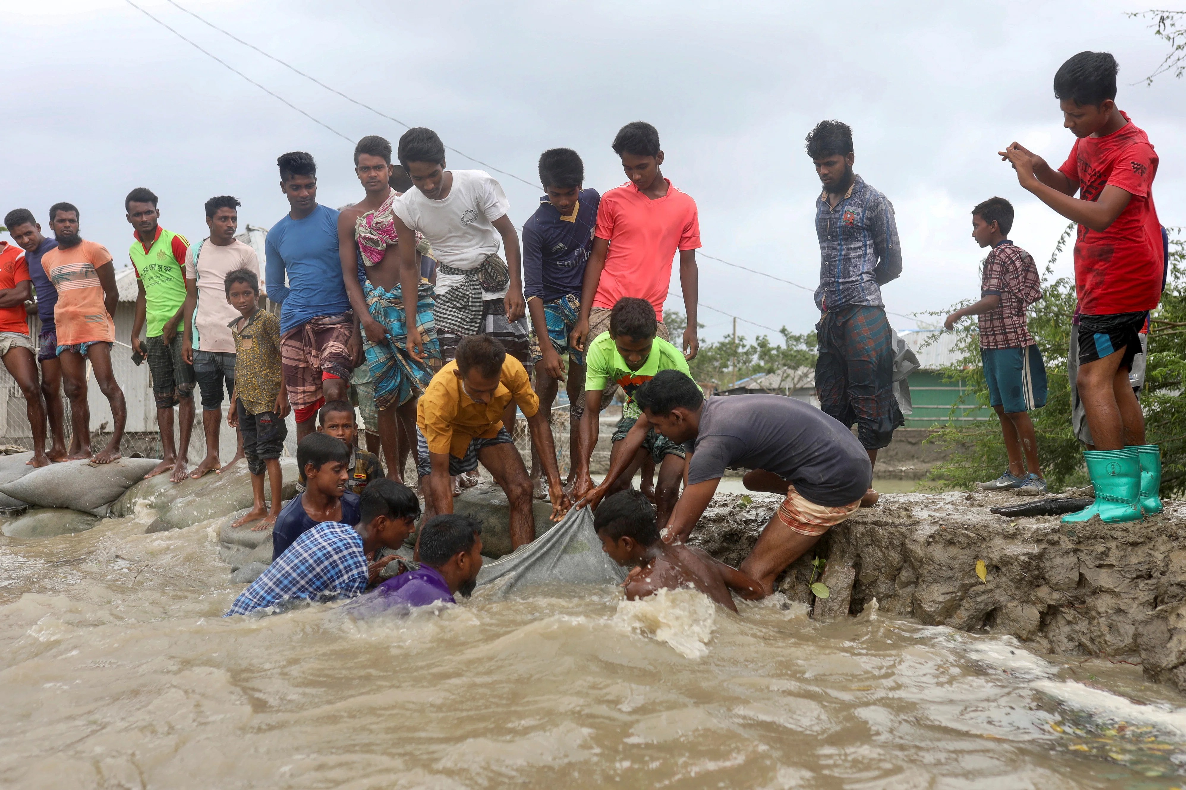 Local people try to enforce the embankment before the cyclone Amphan makes its landfall in Gabura outskirts of Satkhira district on 20 May 2020.