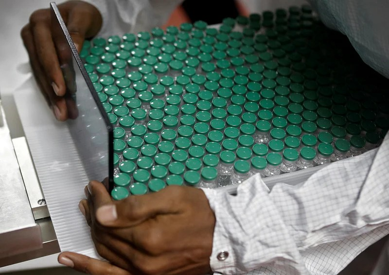An employee in personal protective equipment (PPE) removes vials of AstraZeneca's COVISHIELD, coronavirus disease (COVID-19) vaccine from a visual inspection machine inside a lab at Serum Institute of India, in Pune, India, on 30 November 2020