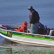 A green police trooper rides a boat in Brazil.