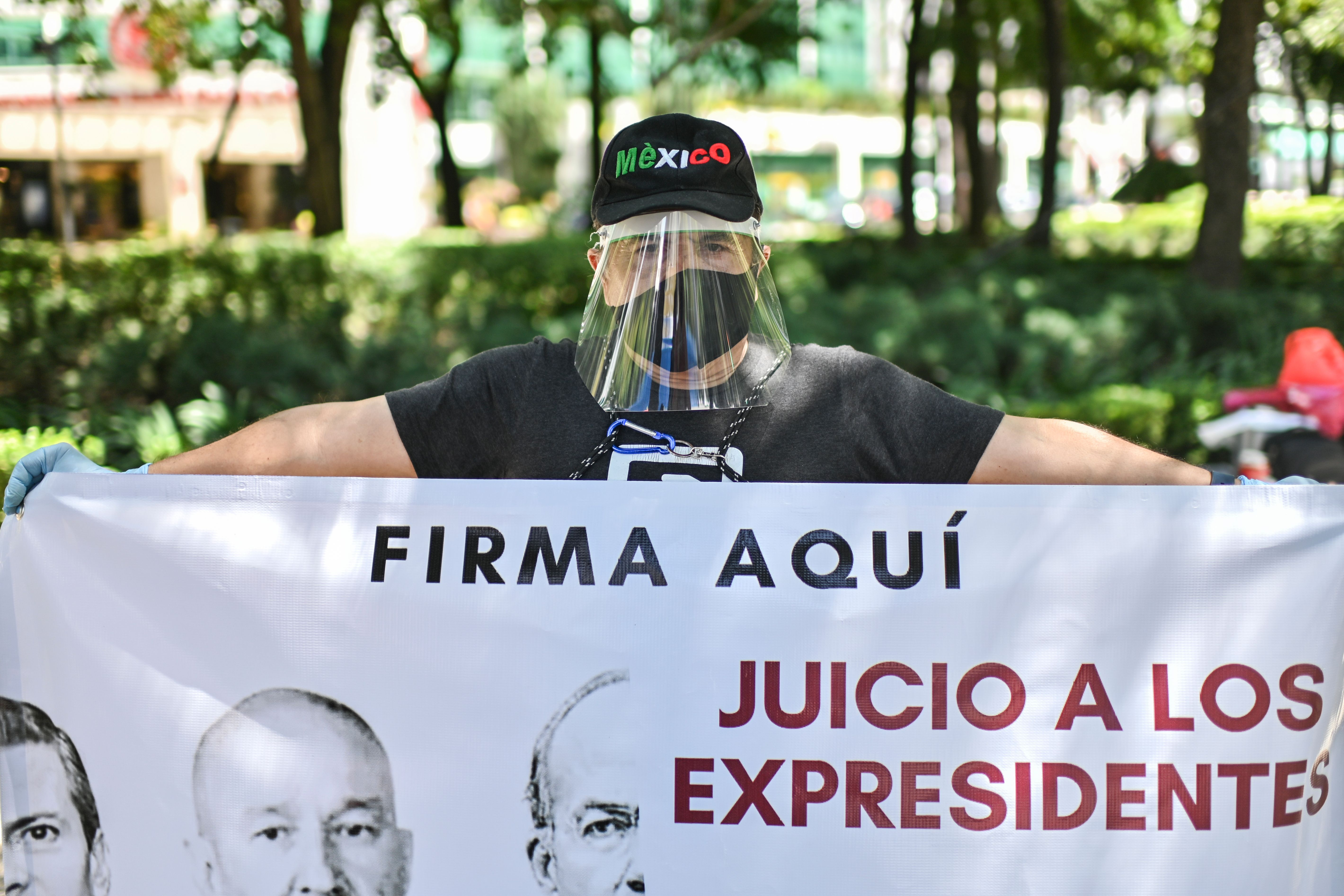 Man in face mask and face shield holds a sign reading 'trials for ex-presidents - sign here'