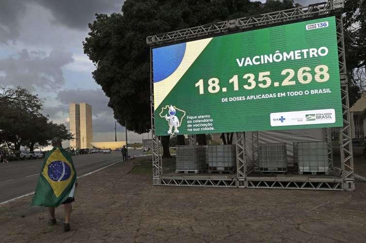 Hombre con capa con la bandera de Brasil pasa junto a una valla publicitaria que muestra un total acumulado del lanzamiento de la vacuna de Brasil.