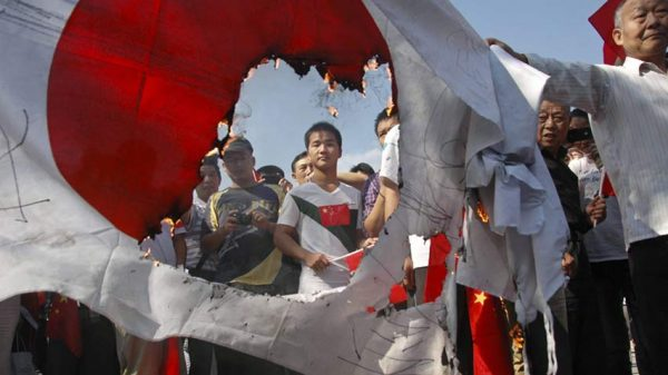 Chinese protesters are burining the national flag of Japan.