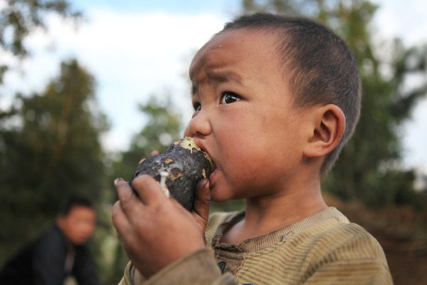 A little child is eating a potato which is provided by a local resident.