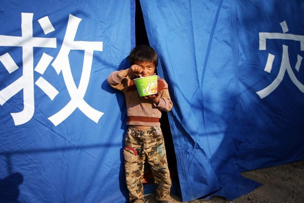 A boy is having instant noodles in front of a relief tent.