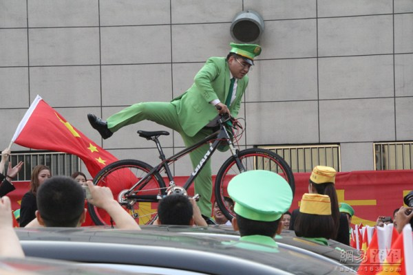 Chen Guangbiao is showing off his bicycle stunt on a car roof.