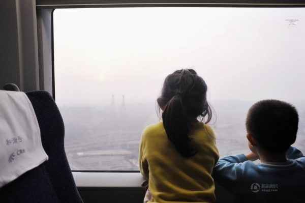 The two kids are absorbed by the view outside the window.