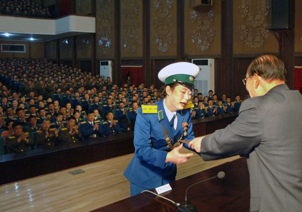 "Pyongyang, North Korea, female traffic officer Ri Kyong Sim crying and wailing as she receives the rare ""Hero of the Republic"" award and honor for protecting a senior government official."