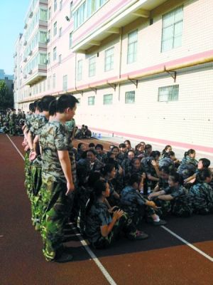 A row of Chinese high school boys formed a wall, using their own shadows to shade their female classmates from the sun during a hot military field day exercise.