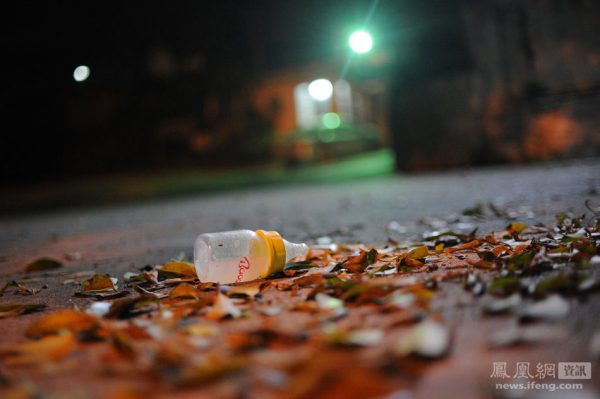 A discarded feeding-bottle among fallen leaves.