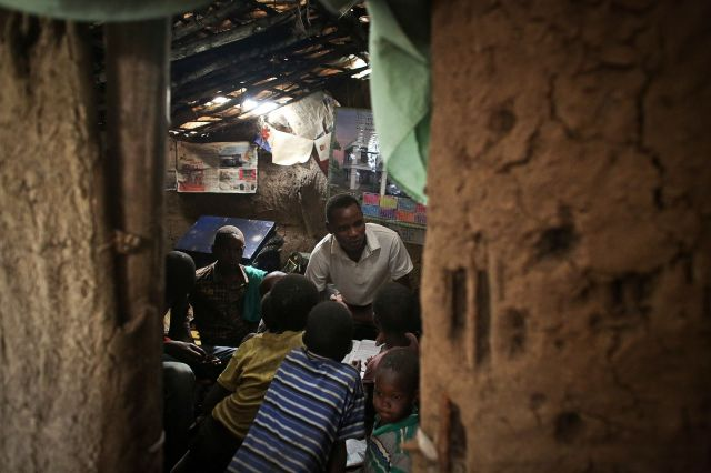 "<span class='image-component__caption' itemprop=""caption"">John Keko Mututua, 16, studies with children from the village in his small hut in the town of Suswa, Kenya. Power provides myriad opportunities, both large and small, to rural parts of Africa. </span>"