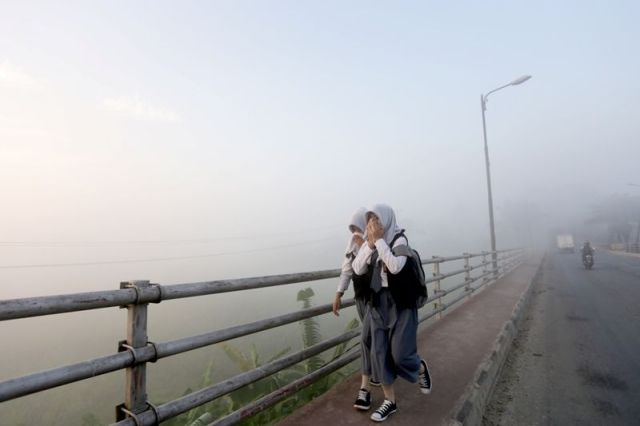 Pelajar SMA melintasi jalan yang dipenuhi kabut asap. (Foto: dok. Okezone)