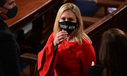"""Rep. Marjorie Taylor Greene (R-Ga.) wears a """"Trump Won"""" face mask as she arrives on the floor of the House to take the oath office on the year's opening session in Washington on Jan. 3, 2021. Greene has said she will introduce a resolution calling for the impeachment of Joe Biden on Jan. 21. (Erin Scott/Pool/Getty Images)"""