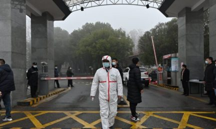 A guard wearing a protective gear is seen at the entrance of the Hubei provincial centre for disease control and prevention as members of the World Health Organization (WHO) team investigating the origins of the Covid-19 coronavirus, visit the place in Wuhan, China's central Hubei province on February 1, 2021. (Photo by HECTOR RETAMAL / AFP) (Photo by HECTOR RETAMAL/AFP via Getty Images)