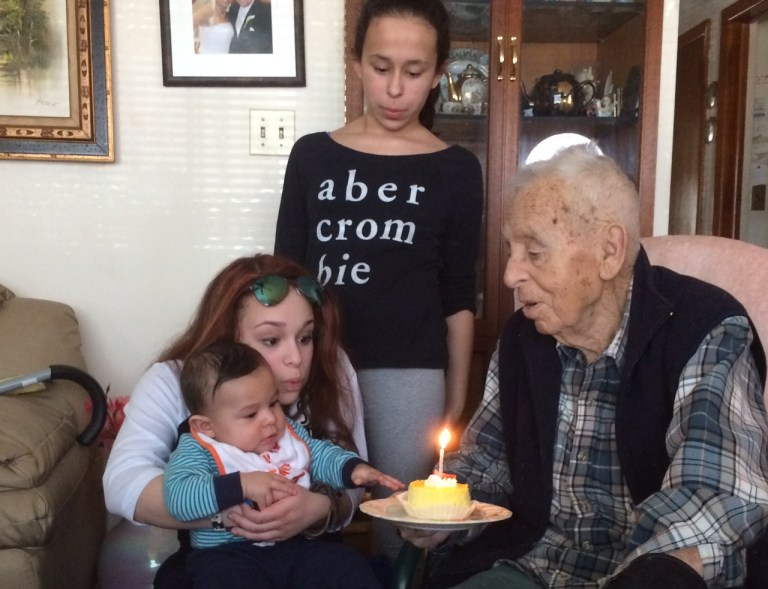 Dad blowing with his three grandchildren getting ready to blow out a pre-birthday candle.