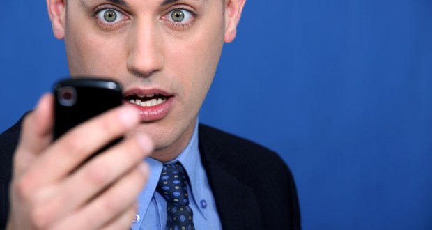 Shocked man looking at mobile telephone
