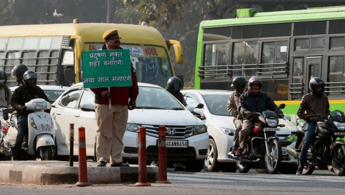"A policeman holding a sign that reads, ""We'll make it a pollution free city, we'll enjoy the new year"" (Image by Delhi government)"