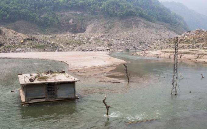 A house and an electric pole under the water due to the dam created by the Jure landslide in Bhotekoshi River in 2014 at Sindhupalchowk, Nepal (Photo by Nabin Baral)