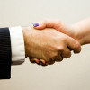 A woman and man shake hands, start networking, and developing understanding through thoughtful conversation.