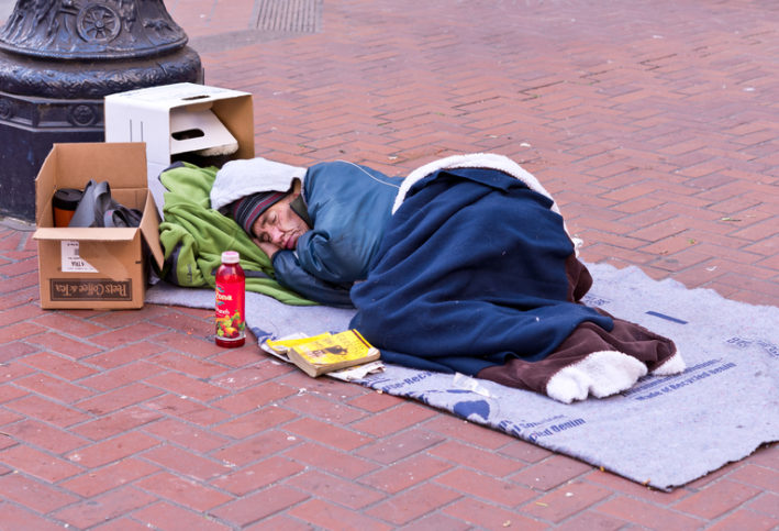 A photo of a homeless man sleeping on a street in San Francisco.