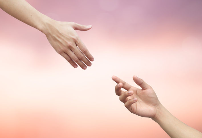 A human hand reaching out towards another.