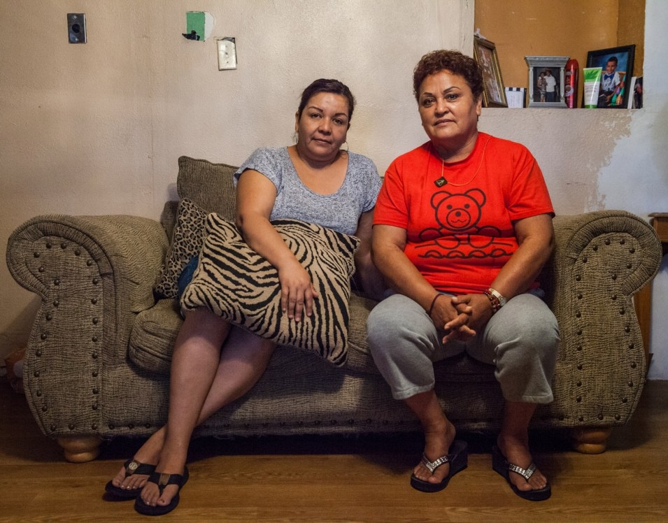 """Tornillo, Texas, residents Lorena Hernandez (left) and Rosa Maria Peña sit for a portrait. """"You get used to it. You work every day and come back really tired,"""" Peña said about having contaminated tap water. She used to be an assembly worker. Hernandez is a seasonal pecan farmworker. (Maria Esquinca/News21)"""
