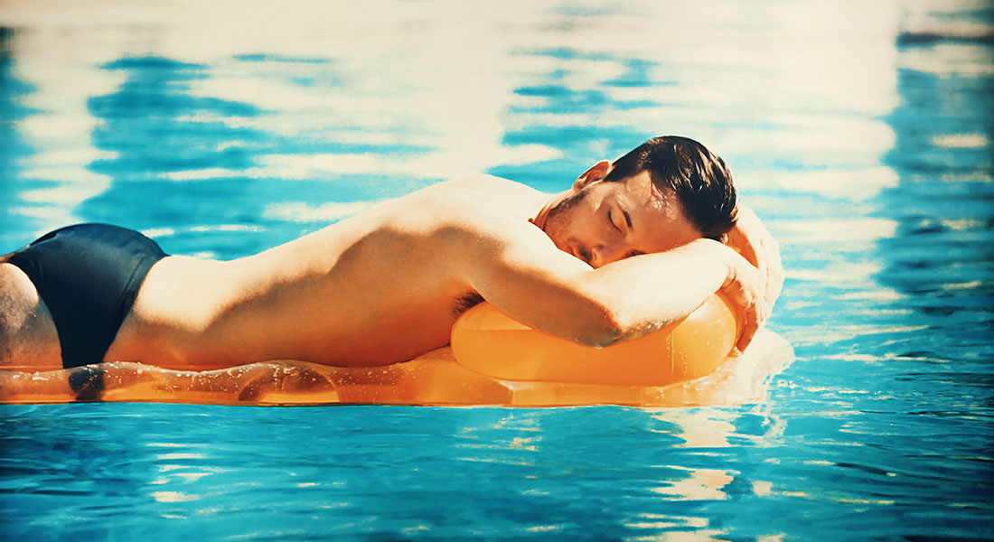 Closeup side view of handsome late 20's man drigting on a yellow pool raft and taking a nap during hot summer afternoon at a pool area. He has brown hair and wearing black speedos.