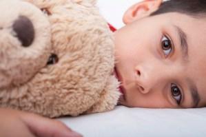 boy-laying-down-with-teddybear