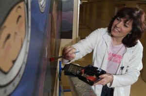 """Artist Susan Farkas paints """"The Journey,"""" a mural at Akron Children's Beeghly campus in the hallway that connects Building B and D."""