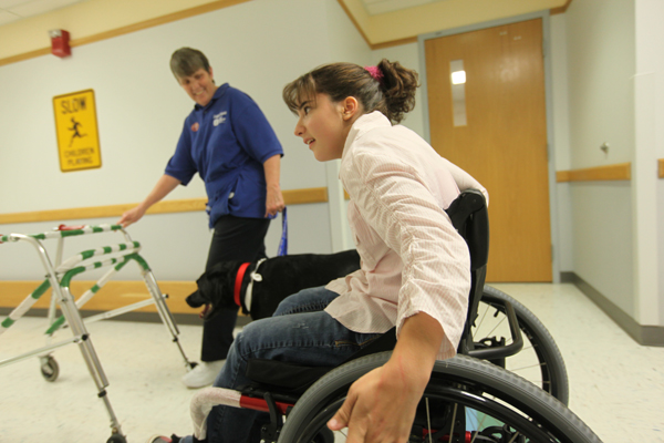 Doggie Brigade handler Chris Witschey has 3 dogs that help kids perform physical therapy.