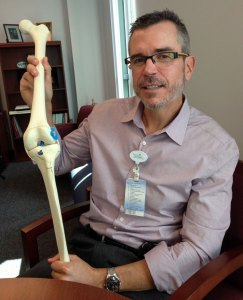 Dr. Jones holding a model of  a knee featuring an ACL repair.