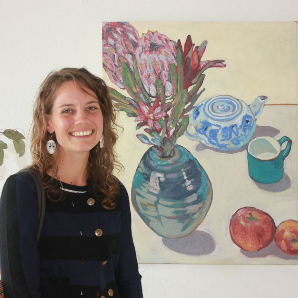 Dubbo artist Matilda Julian with an oil painting from her Fields and Flowers exhibition