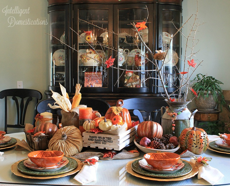 Our Farmhouse Style Fall Tablescape is made up of lots of pumpkins, a wood crate, an antique dough bowl, a vintale metal milk can and more