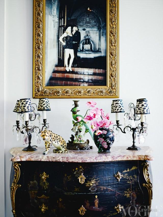 Entrada con cómoda antigua policromada, lámparas, figuras, flores, foto enmarcada en dorado.