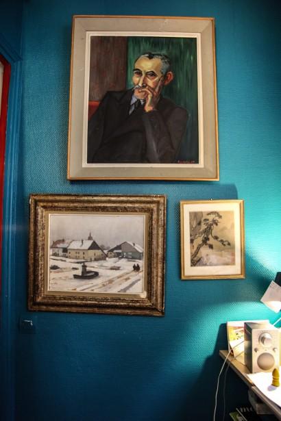 La pared azul hace resaltar los cuadros y dibujos.