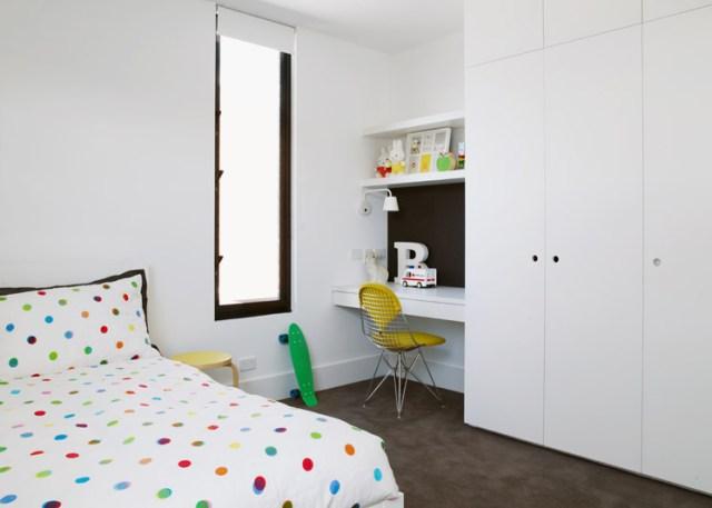 Dormitorio juvenil con el mobiliario diseñado a medida, el suelo continuo en un marrón que contrasta con los elementos blancos.