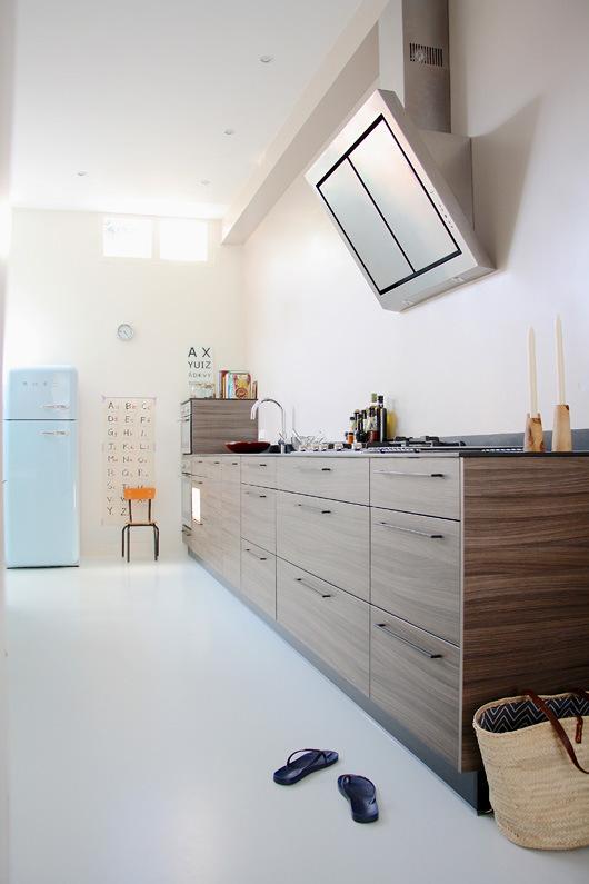 La cocina tiene un diseño limpio sin muebles en la parte superior. El suelo de toda la vivienda es continuo, pintado blanco, lo que da mucha luz al interior.