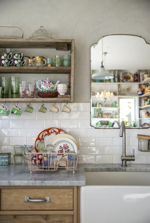 En la cocina se ha colocado un espejo porque la propietaria añoraba tener ahí una ventana, y porque así puede también ver a sus hijas mientras juegan.